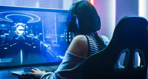 girl playing on a modern gaming monitor